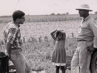 """Opelousas, La. Area, St. Landry Parish, May 31, 1966. On his regular rounds of seeing farmers, CORE task force worker talks with Joseph Malbrough, President of the Grand Marie Co-op, on his farm. Between them is Malbrough's daughter."" Image from the personal papers of Ronnie Moore."